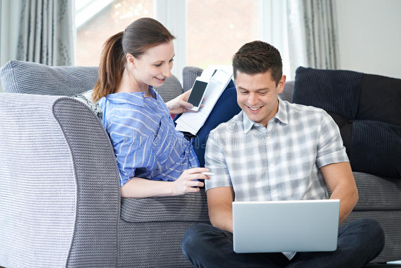 Pares autônomos que trabalham da casa que olha o portátil junto foto de stock