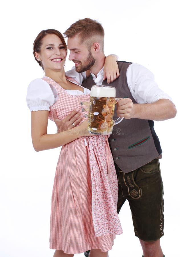 Pares bávaros en traje tradicional con la cerveza y el brezel imagen de archivo