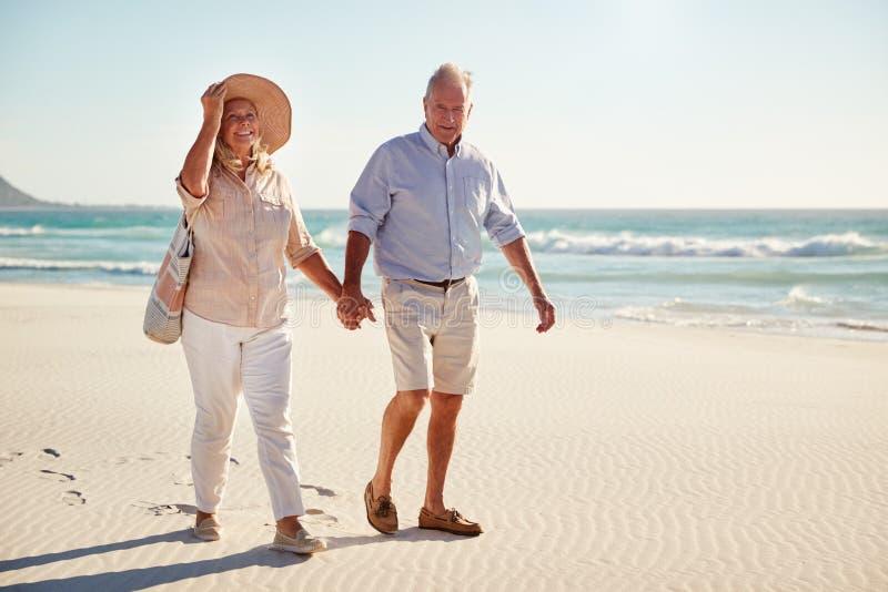 Pares blancos mayores que caminan en una playa juntas que levanta las manos, integrales, cierre imagenes de archivo