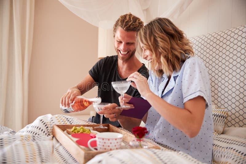Pares blancos milenarios que celebran con champán, el desayuno y los regalos en la cama, cierre para arriba imagen de archivo