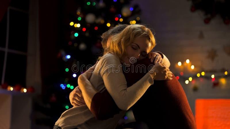 Pares blandos impresionantes que abrazan cerca del árbol de navidad, celebrando día de fiesta, amor foto de archivo libre de regalías