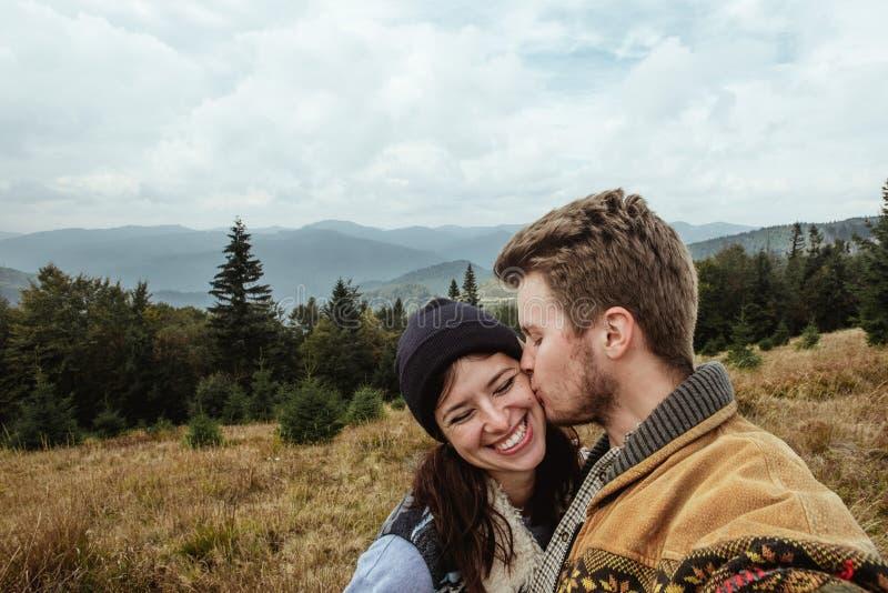 Pares blandos que viajan hermosos elegantes que se besan en el mountai foto de archivo libre de regalías