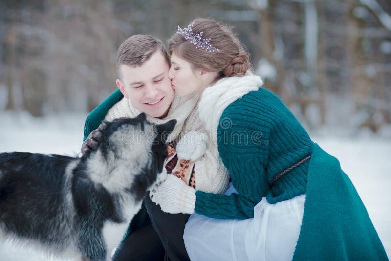 Pares bonitos com o cão de puxar trenós Siberian na floresta nevado do inverno fotos de stock royalty free