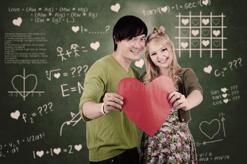 Pares Bonitos Com O Cartão Do Coração Do Valentim Imagens de Stock