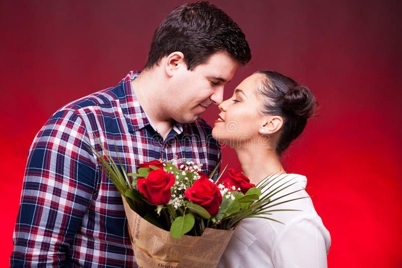 Pares bonitos com um ramalhete das rosas nas mãos fotos de stock