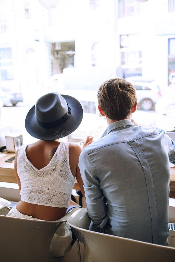 Pares bonitos da vista traseira na rua no café foto de stock