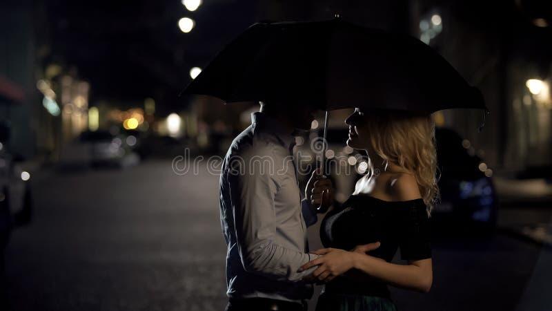 Pares bonitos de amantes que abra?am sob o guarda-chuva, data da noite, hist?ria de amor imagens de stock royalty free