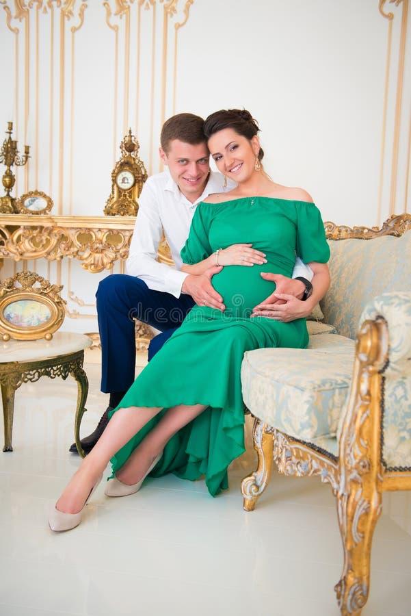 Pares bonitos de pais em antecipação à criança Coração na barriga grávida imagem de stock