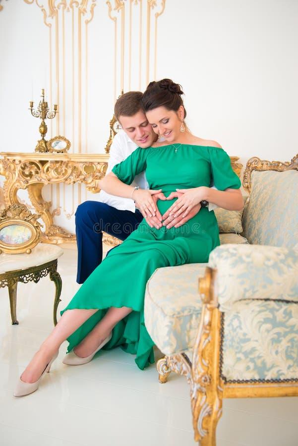 Pares bonitos de pais em antecipação à criança Coração na barriga grávida fotografia de stock royalty free