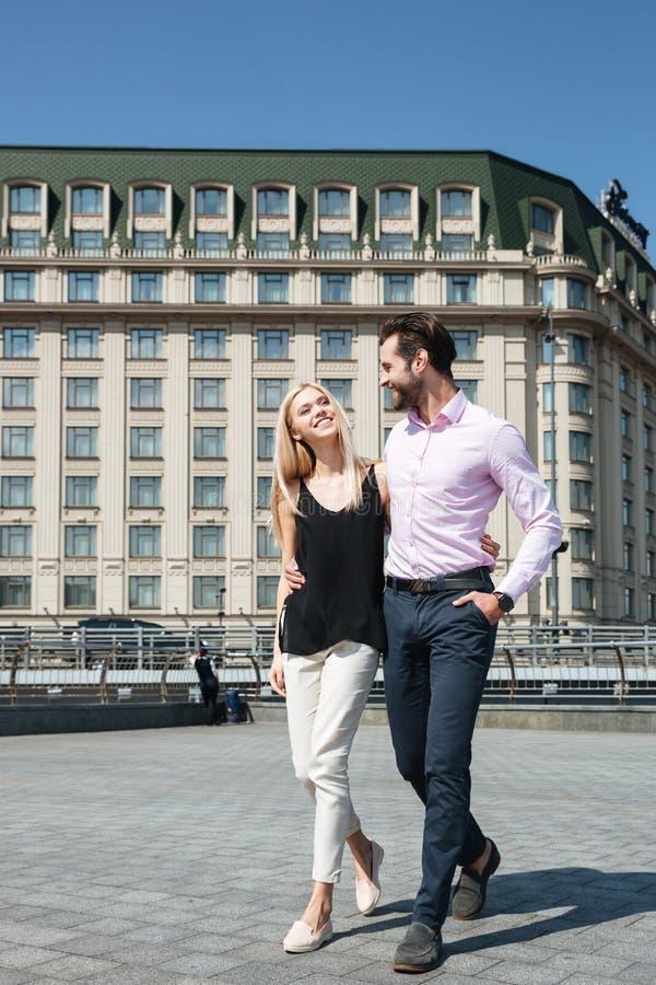 Pares bonitos del hombre alegre y de la mujer que caminan en calle foto de archivo libre de regalías