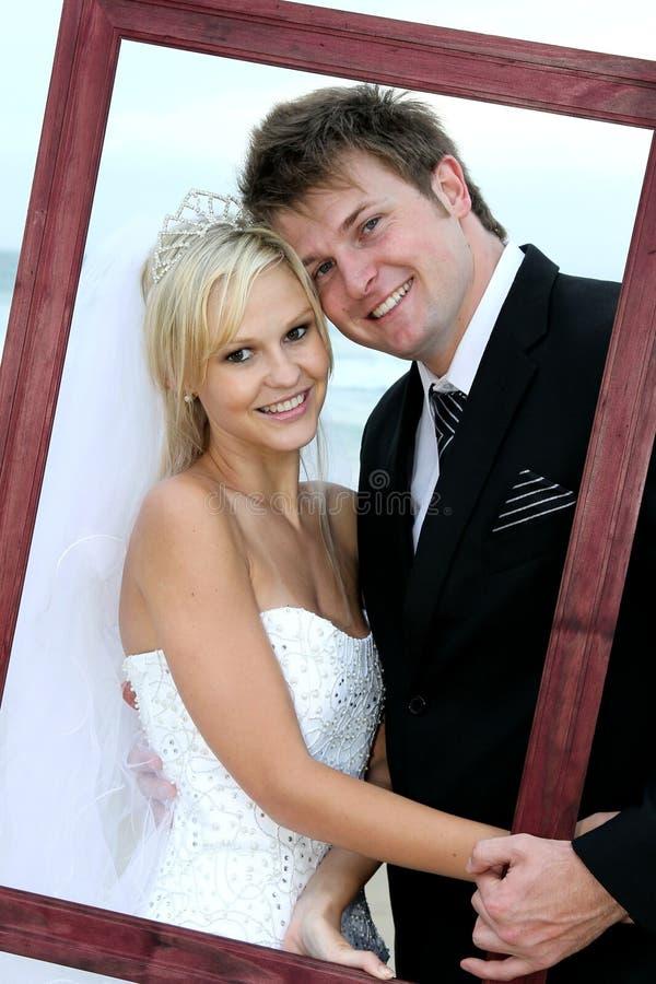 Pares bonitos do casamento com frame imagem de stock royalty free