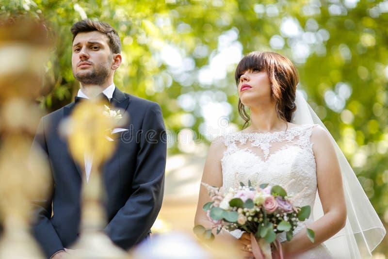 Pares bonitos do casamento na cerimônia da igreja fotografia de stock