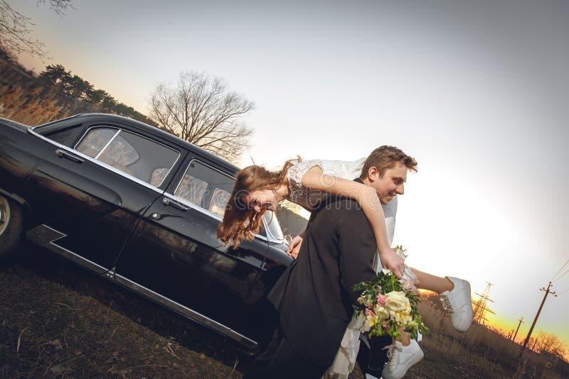 Pares bonitos do casamento no campo ao lado do carro retro o noivo do homem está tomando guardando a noiva em seus braços ch feli fotografia de stock royalty free