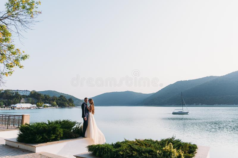 Pares bonitos do casamento, noivos que guardam as mãos em um fundo do lago Menina bonito no vestido branco, homens no preto fotos de stock royalty free