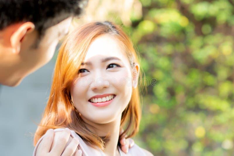 Pares bonitos do retrato que olham cada outro olhos e que sorriem com o homem asiático feliz, novo e a relação da mulher com data foto de stock royalty free