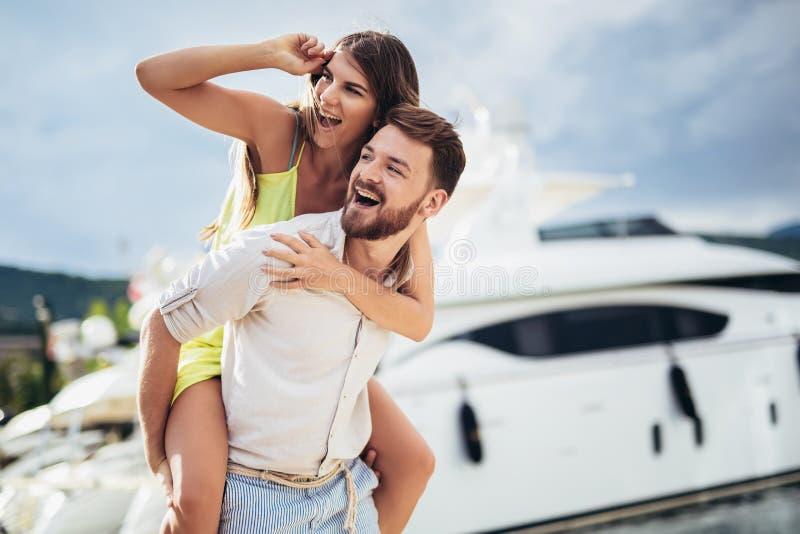 Pares bonitos do turista que apreciam férias de verão no beira-mar Menina alegre que reboca no noivo novo fotografia de stock
