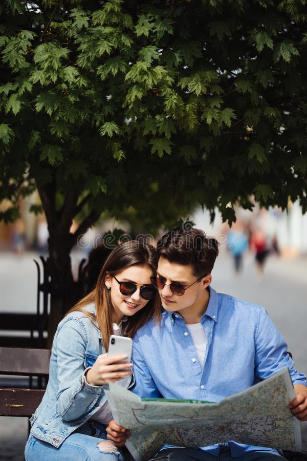 Pares bonitos do turista que viajam usando o mapa e o telefone Retrato do homem e da jovem mulher de sorriso que estão na rua, pr foto de stock