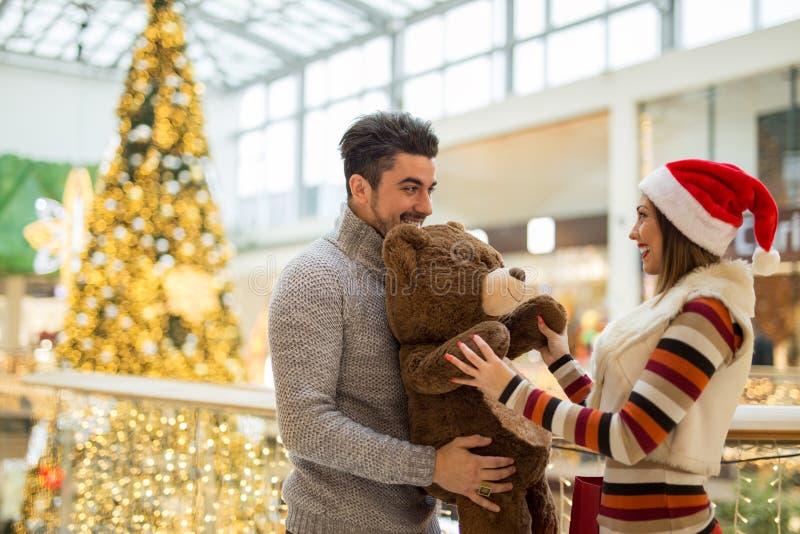 Pares bonitos em um shopping para o Natal com uma peluche b fotos de stock
