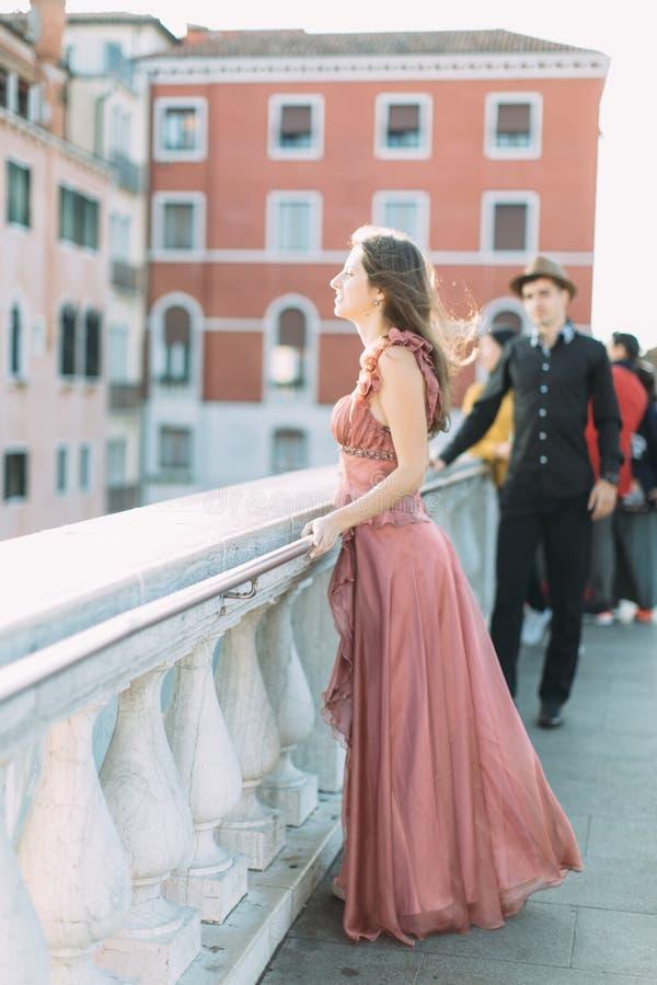 Pares bonitos em Veneza Moça bonita na posição cor-de-rosa longa do vestido na ponte do canal venetian, homem novo na roupa preta imagens de stock royalty free