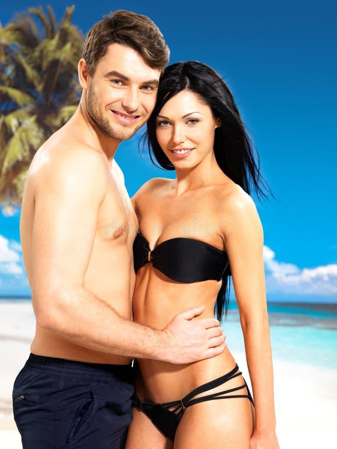 Pares bonitos felizes no amor na praia tropical imagens de stock