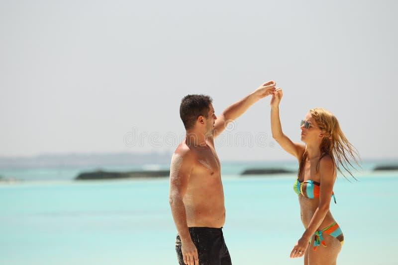 Pares bonitos felizes que apreciam na praia no dia ensolarado h de Maldivas fotos de stock