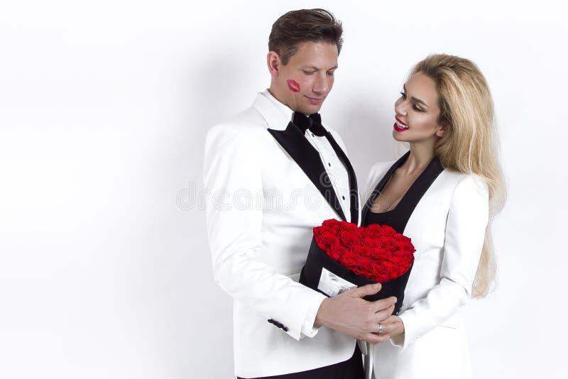 Pares bonitos felizes que levantam no fundo branco e que guardam a caixa da flor com coração vermelho Dia do ` s do Valentim, cas imagem de stock