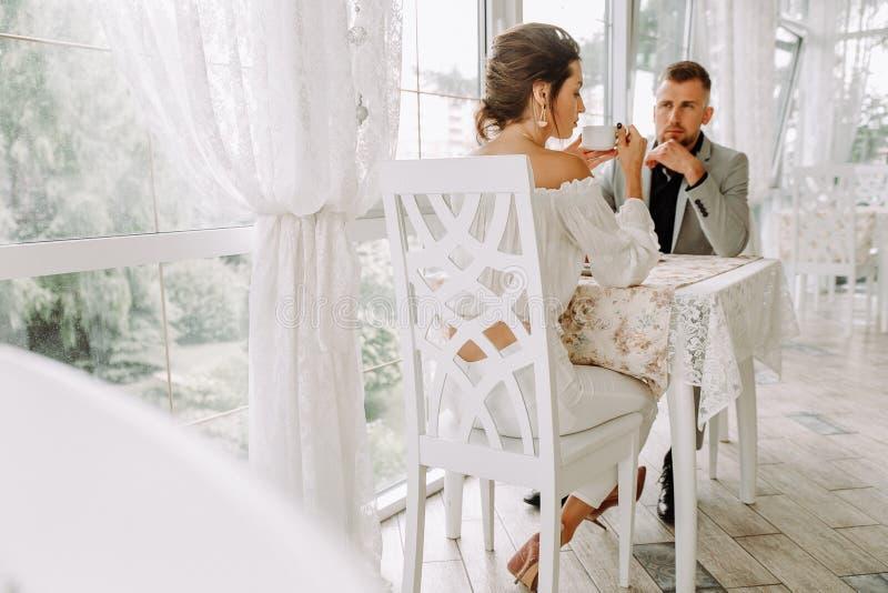 Pares bonitos felizes que sentam-se em um restaurante e em uma fala fotografia de stock