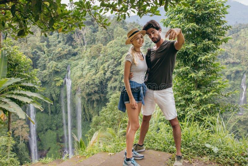 Pares bonitos junto no penhasco que toma o selfie com cachoeira imagem de stock royalty free