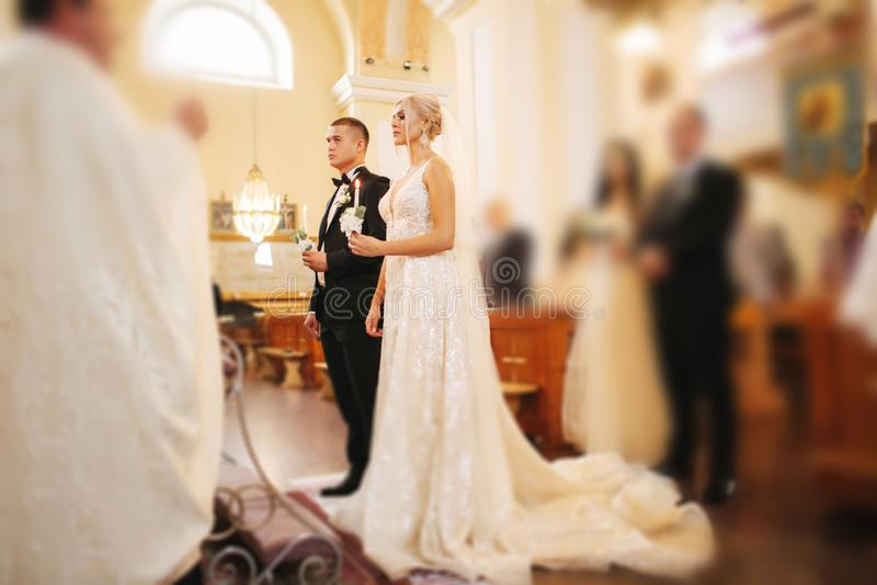 Pares bonitos na igreja Os recém-casados juram entre si para amar para sempre Noiva e noivo felizes foto de stock royalty free