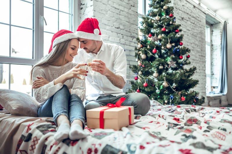 Pares bonitos no amor, chapéus vestindo de Santa, sentando-se ao lado de uma árvore de Natal agradavelmente decorada e fazendo um foto de stock royalty free