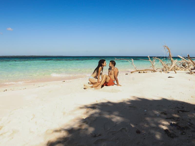 Pares bonitos no Sandy Beach, na água de turquesa e nas palmeiras brancos na ilha de Onok em Balabac, Palawan em Filipinas foto de stock royalty free