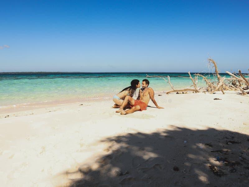 Pares bonitos no Sandy Beach, na água de turquesa e nas palmeiras brancos na ilha de Onok em Balabac, Palawan em Filipinas imagem de stock