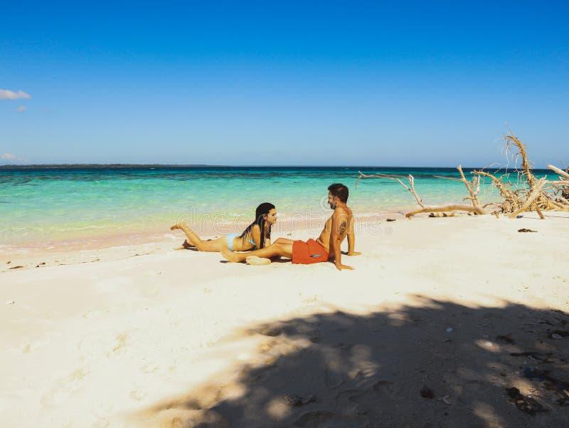 Pares bonitos no Sandy Beach, na água de turquesa e nas palmeiras brancos na ilha de Onok em Balabac, Palawan em Filipinas fotos de stock royalty free