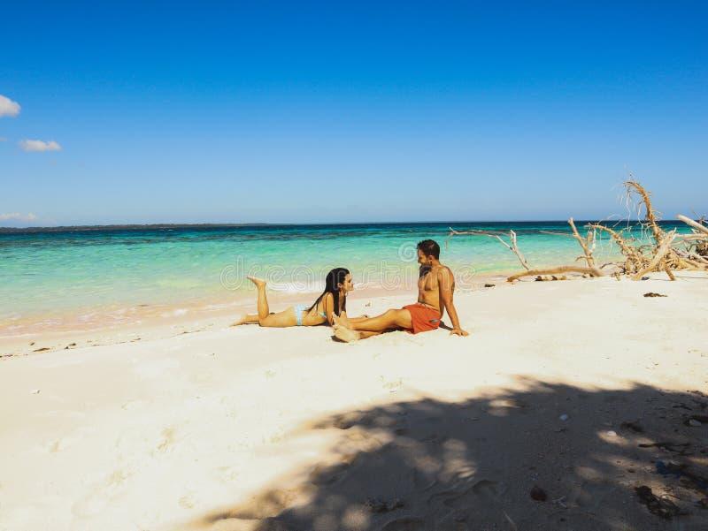 Pares bonitos no Sandy Beach, na água de turquesa e nas palmeiras brancos na ilha de Onok em Balabac, Palawan em Filipinas imagens de stock