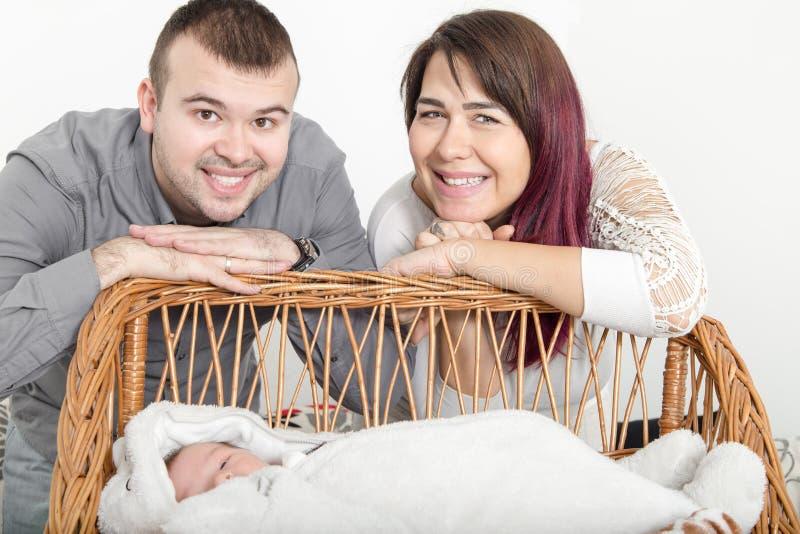 Pares bonitos novos com bebê novo em casa fotos de stock