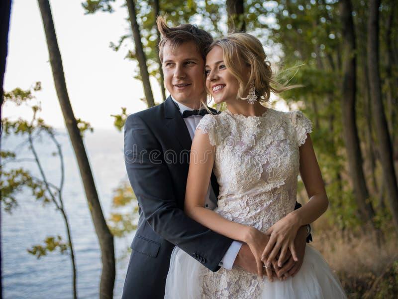 Pares bonitos, novos do casamento no fundo de n bonito foto de stock
