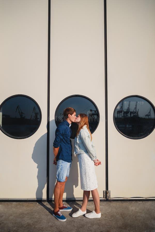 Pares bonitos novos bonitos do moderno que beijam no porto, na parede branca com fundo grande das vigias imagem de stock