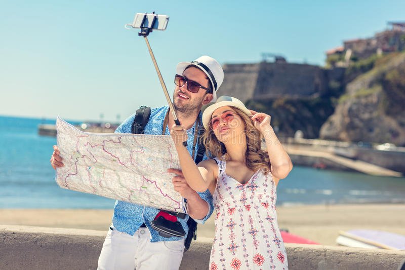 Pares bonitos novos do turista dos amigos e tomada da imagem da vara do selfie junto na cidade feliz no dia ensolarado fotos de stock royalty free