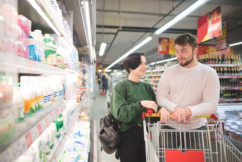 Pares bonitos novos em um supermercado perto do contador Acople com um carro leva a compra em um supermercado foto de stock royalty free