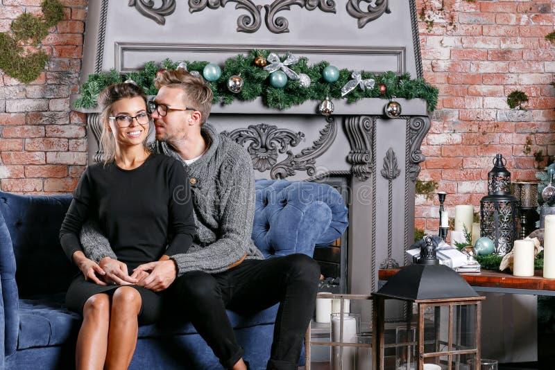 Pares bonitos novos na sala do sótão com parede de tijolo Ano novo feliz Árvore de Natal decorada imagem de stock