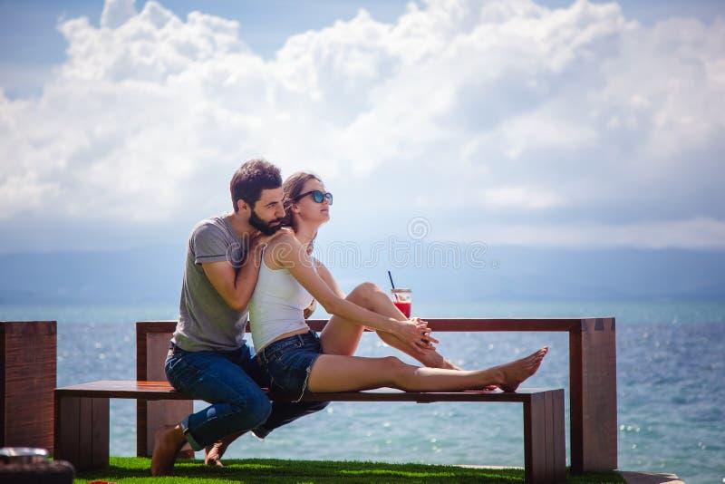 Pares bonitos novos no amor no mar tropical no café da praia, fotografia de stock