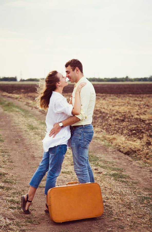 Pares bonitos novos que abraçam na estrada rural durante a viagem romântica com mala de viagem marrom imagem de stock royalty free
