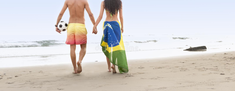 Pares bonitos novos que andam ao longo da praia com bandeira e futebol de Brasil fotografia de stock