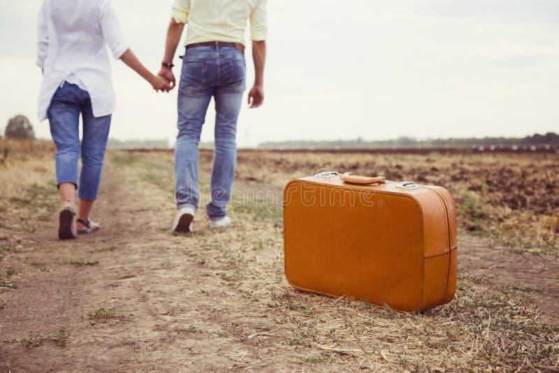 Pares bonitos novos que andam e que guardam as mãos na estrada rural durante a viagem romântica com mala de viagem marrom fotos de stock royalty free