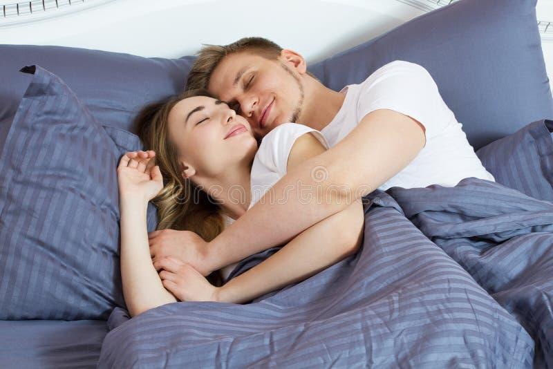 Pares bonitos novos que dormem junto na cama Cama e colchão confortáveis fotos de stock royalty free