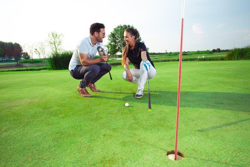 Pares bonitos novos que jogam o golfe na grama imagem de stock