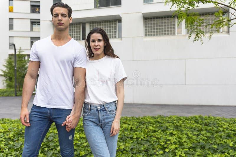 Pares bonitos novos que levantam calças de brim e o t-shirt vestindo imagens de stock royalty free
