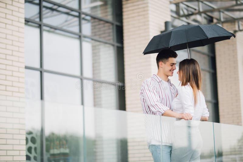 Pares bonitos novos que olham se com amor sob o guarda-chuva no dia chuvoso na rua Relacionamento do amor e dos pares imagem de stock