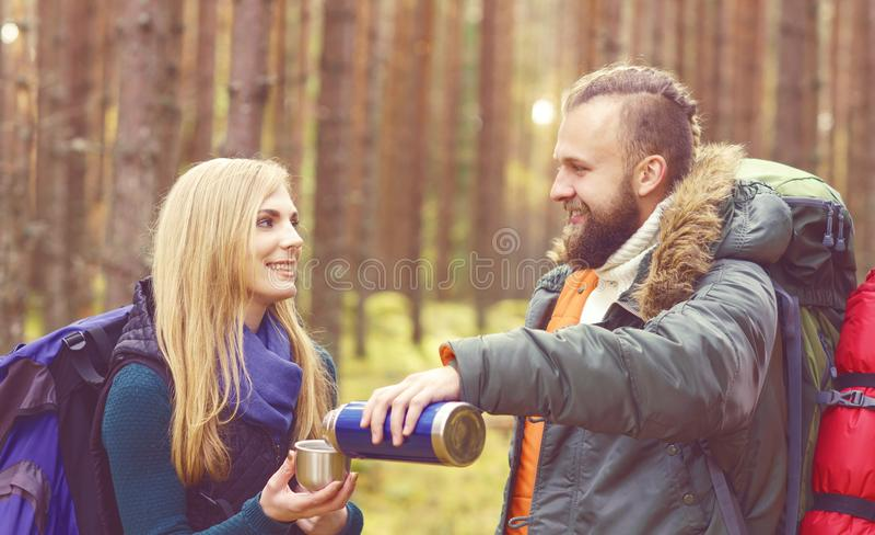 Pares bonitos novos que têm uma ruptura na floresta e que bebem um t fotografia de stock royalty free