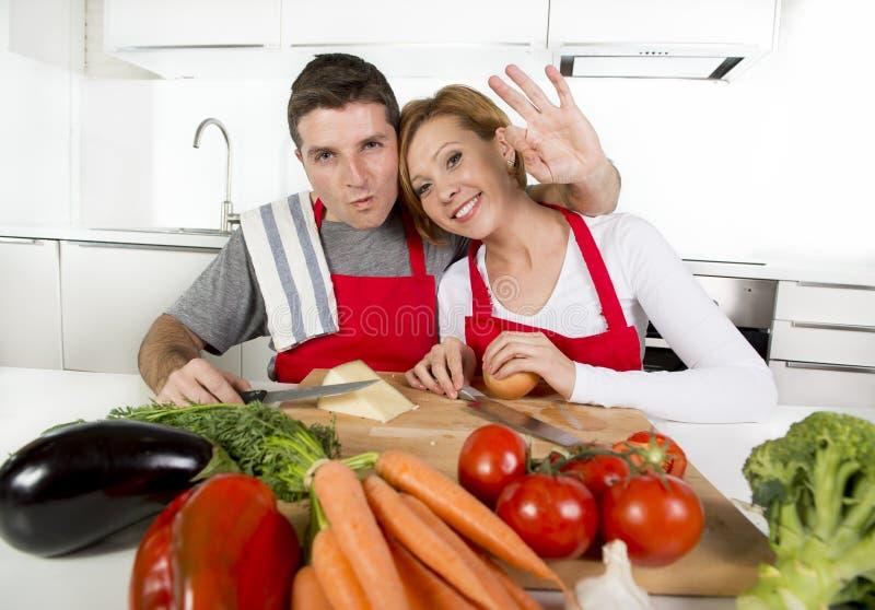 Pares bonitos novos que trabalham em casa a cozinha que prepara o sorriso vegetal da salada junto feliz foto de stock
